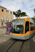 A modern tram in Lisbon, it is green